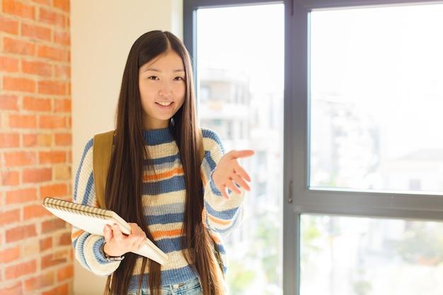 Jeune femme asiatique souriant, vous saluant et vous offrant une poignée de main pour conclure un accord réussi, concept de coopération