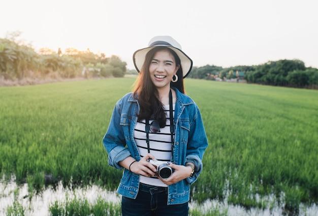 Jeune femme asiatique souriante au chapeau avec caméra. fille profitant de la belle nature avec le coucher du soleil.
