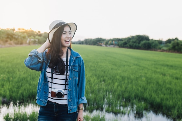 Jeune femme asiatique souriante au chapeau avec caméra. fille profitant de la belle nature avec sunse