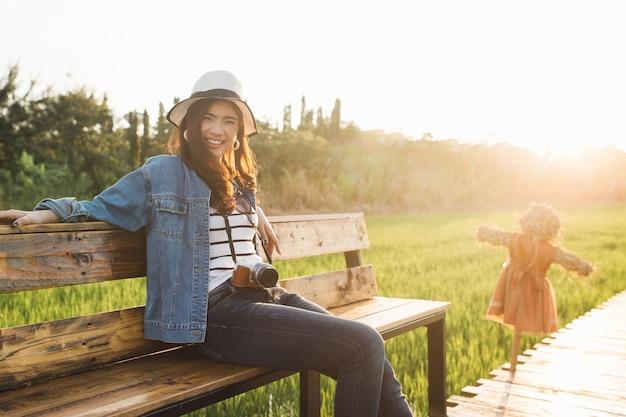 Jeune femme asiatique souriante au chapeau avec caméra.