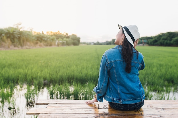Jeune femme asiatique souriante au chapeau. fille profitant de la belle nature avec le coucher du soleil.