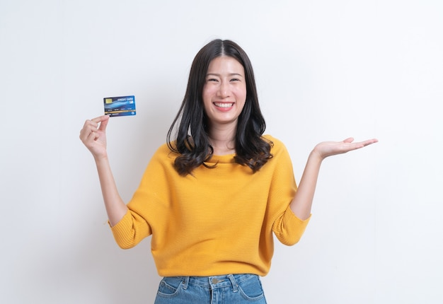 Jeune femme asiatique souriante et belle présentant la carte de crédit en main montrant la confiance et la confiance pour effectuer le paiement