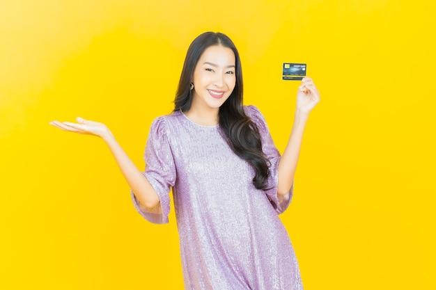 Jeune femme asiatique souriante avec carte de crédit sur jaune