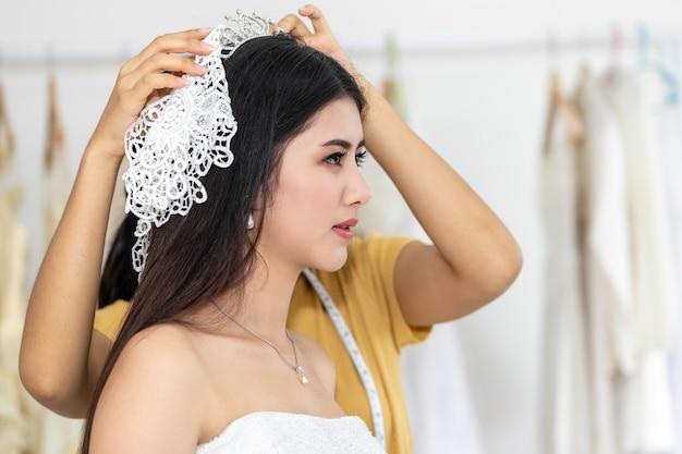 Jeune femme asiatique souriante et essayant la robe de mariée dans un magasin.