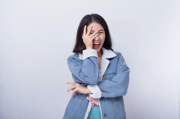 Jeune femme asiatique souriante excitée montrant sa main avec expression se sentir surpris et surpris, positive fille caucasienne heureuse portant portrait de vêtements décontractés bleus