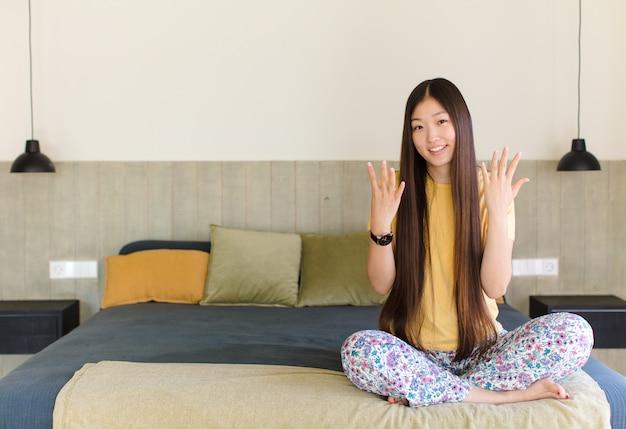 Jeune femme asiatique souriante et à la recherche amicale, montrant le nombre