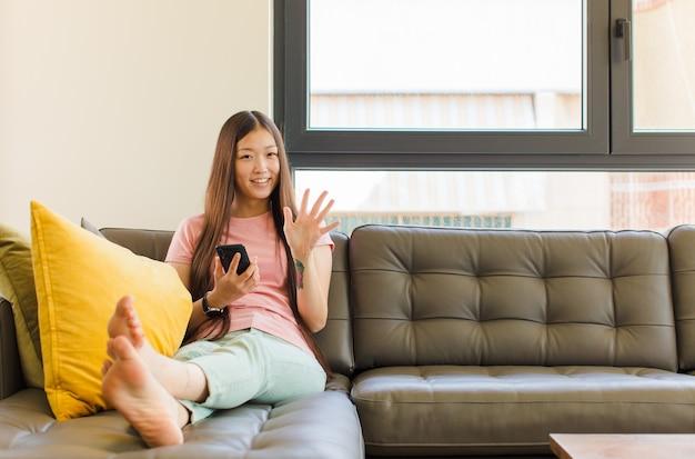 Jeune femme asiatique souriante et à la recherche amicale, montrant le numéro cinq ou cinquième avec la main en avant, compte à rebours