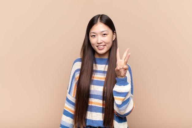 Jeune femme asiatique souriante et à la recherche amicale, montrant le numéro trois ou troisième avec la main en avant, compte à rebours