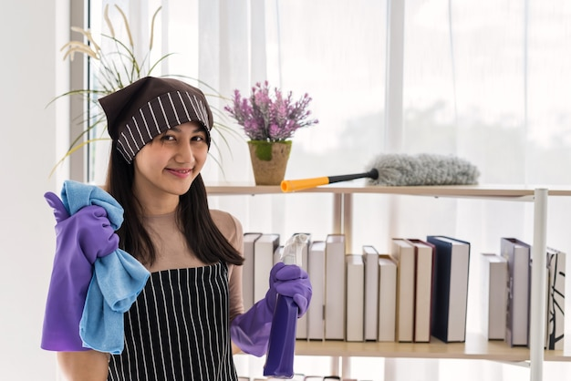 Jeune femme asiatique souriante avec tablier et gant de protection des mains violet pouce vers le haut pendant le nettoyage de la maison. une femme au foyer heureuse tient un spray hygiénique et un chiffon en microfibre pour le nettoyage des tâches ménagères le week-end.