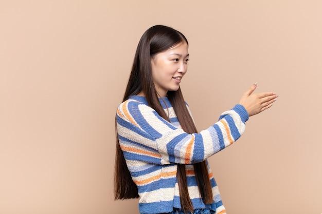 Jeune femme asiatique souriante, vous saluant et offrant une poignée de main pour conclure un accord réussi, concept de coopération
