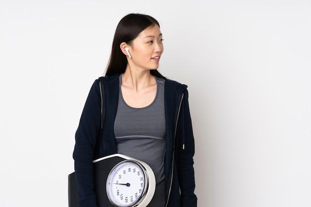 Jeune femme asiatique sport isolé sur blanc avec machine de pesage