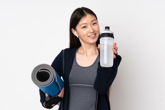 Jeune femme asiatique sport isolé sur mur blanc avec bouteille d'eau de sport et avec un tapis