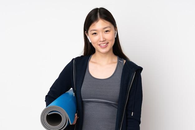 Jeune femme asiatique sport avec un tapis et souriant
