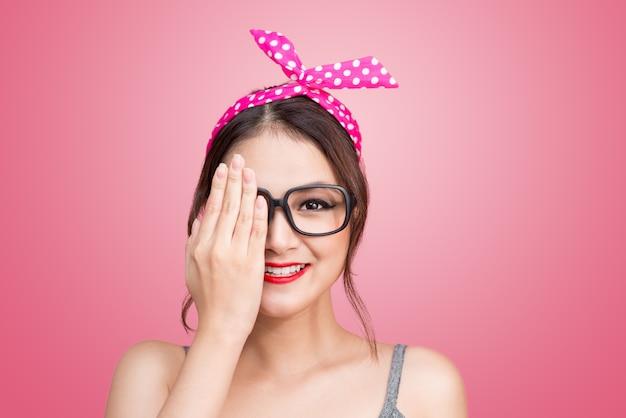 Une jeune femme asiatique de style rétro couvre ses yeux d'une main.
