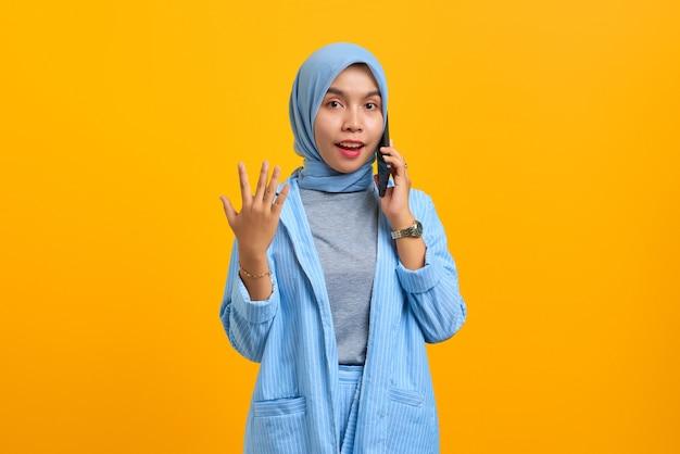 Jeune femme asiatique surprise parlant au téléphone portable et mains levées isolées sur fond jaune