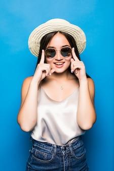 Jeune femme asiatique avec surprise pose isolé sur fond bleu. portrait de la belle femme asiatique en chapeau de paille et lunettes de soleil sur fond bleu
