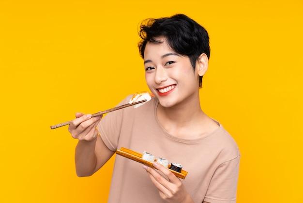 Jeune, femme asiatique, à, sushi, sur, mur jaune