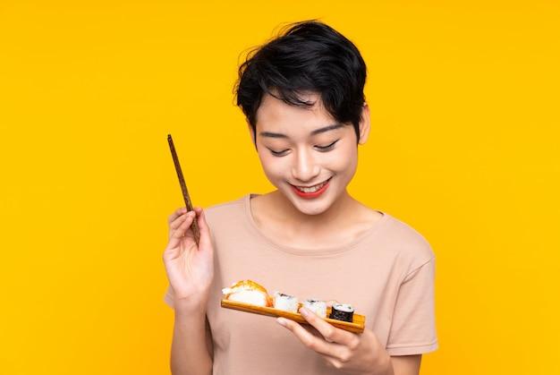 Jeune femme asiatique avec des sushis avec une expression heureuse
