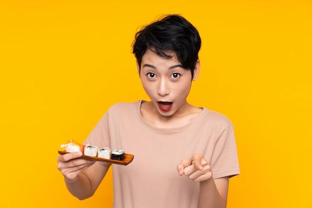 Jeune femme asiatique avec des sushis surpris et pointant vers l'avant