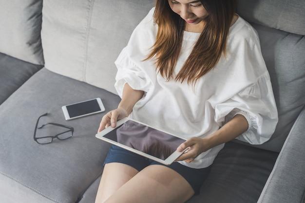 Jeune femme asiatique avec tablette à la maison