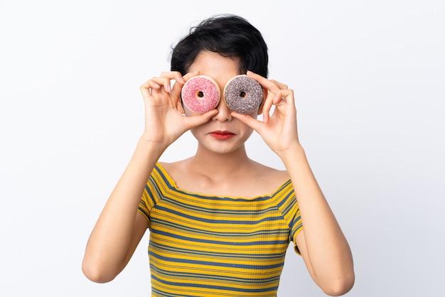 Jeune femme asiatique tenant des beignets dans les yeux avec une expression triste