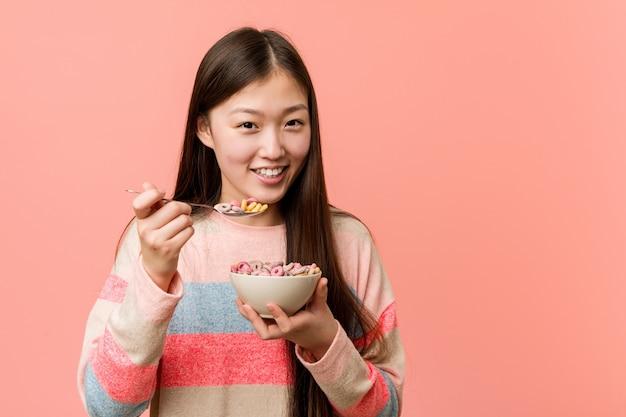 Jeune femme asiatique tenant un bol de céréales