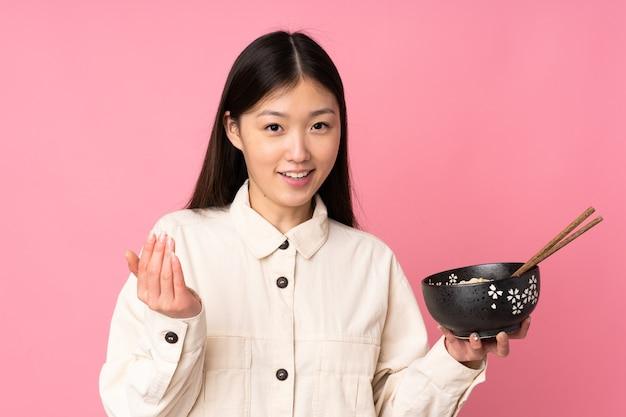 Jeune femme asiatique tenant un bol de nouilles avec des baguettes
