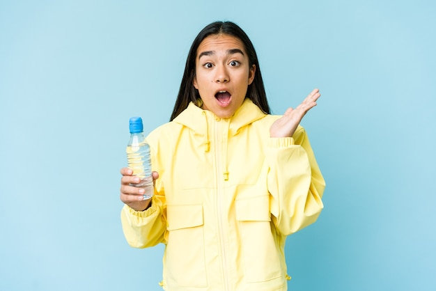 Jeune femme asiatique tenant une bouteille d'eau isolée sur un mur bleu surpris et choqué