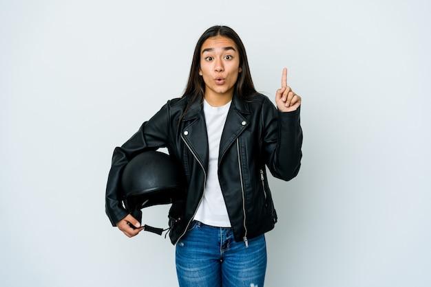 Jeune femme asiatique tenant un casque de moto sur un mur isolé ayant une bonne idée