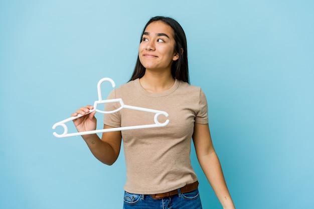 Jeune femme asiatique tenant un cintre isolé sur un mur bleu rêvant d'atteindre les objectifs et buts