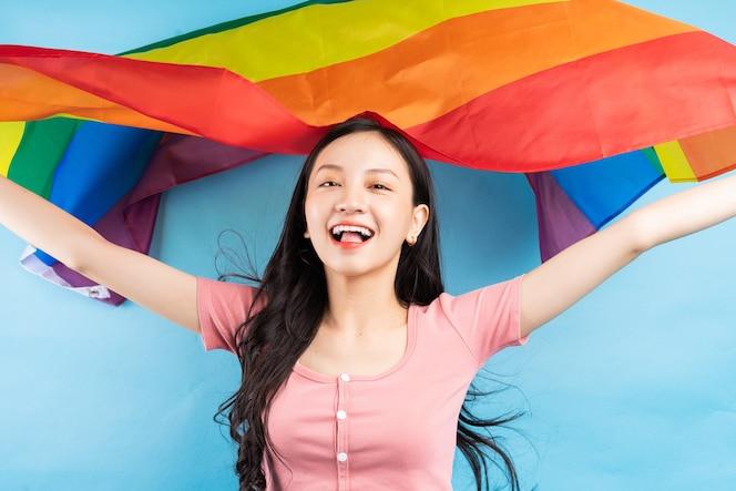 jeune femme asiatique tenant un drapeau arc-en-ciel pour soutenir la communauté lgbtq + sur bleu