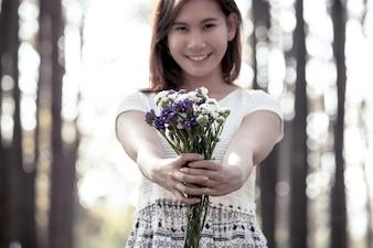 Jeune femme asiatique tenant des fleurs dans le parc en couleur vintage