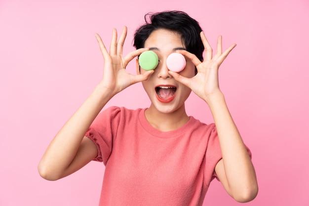 Jeune femme asiatique tenant des macarons français colorés avec une expression surprise