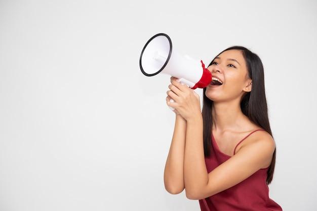 Jeune femme asiatique tenant un mégaphone isolé sur fond blanc, discours et annonce le concept