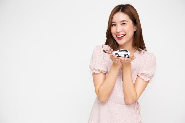 Jeune femme asiatique tenant le modèle de voiture isolé sur fond blanc.