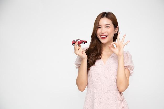 Jeune femme asiatique tenant le modèle de voiture rouge et montrant le signe ok isolé sur fond blanc.