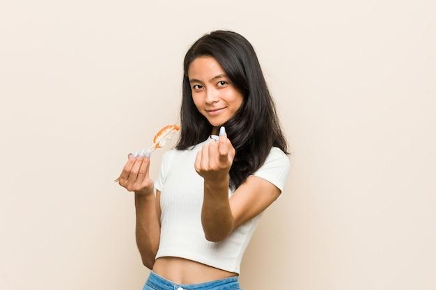 Jeune femme asiatique tenant un morceau de sushi pointant avec le doigt vers vous comme si vous vous invitiez à vous rapprocher.