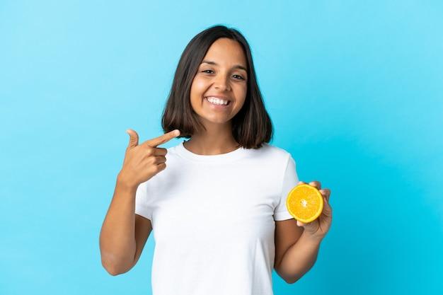 Jeune femme asiatique tenant une orange isolée sur bleu donnant un geste de pouce en l'air