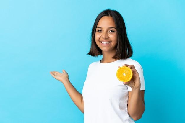 Jeune femme asiatique tenant une orange isolée sur bleu s'étendant les mains sur le côté pour inviter à venir