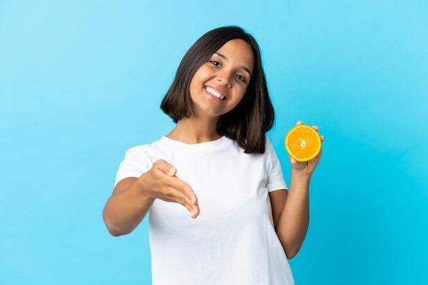 Jeune femme asiatique tenant une orange isolée sur bleu serrant la main pour conclure une bonne affaire