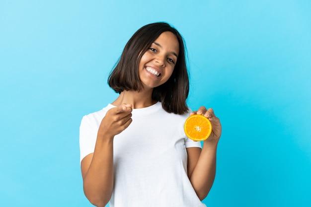 Jeune femme asiatique tenant une orange isolée sur le devant de pointage bleu avec une expression heureuse