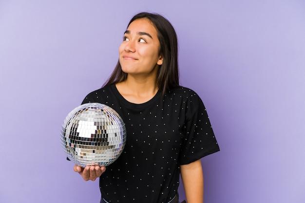 Jeune femme asiatique tenant une partie de balle isolée rêvant d'atteindre les objectifs et buts