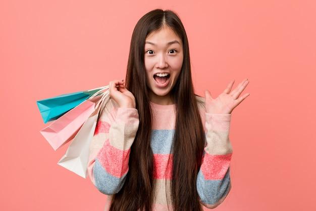 Jeune femme asiatique tenant un sac de shopping célébrant une victoire ou un succès