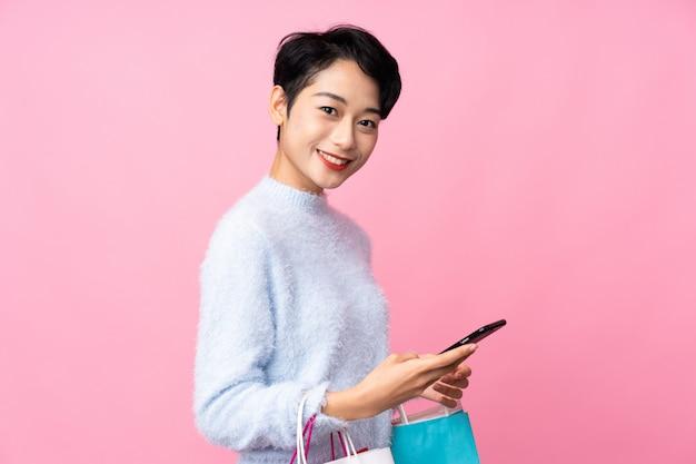 Jeune femme asiatique tenant des sacs à provisions et écrivant un message avec son téléphone portable à un ami