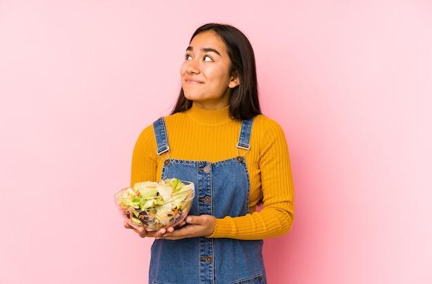 Jeune femme asiatique tenant une salade isolée rêvant d'atteindre les objectifs et les buts