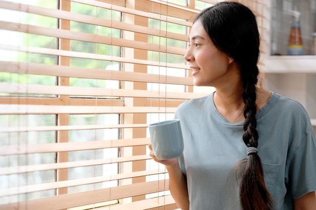 Jeune femme asiatique tenant une tasse de café en se tenant debout dans la cuisine à la maison