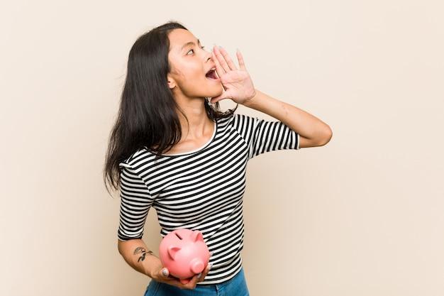 Jeune femme asiatique tenant une tirelire criant et tenant la paume près de la bouche ouverte.