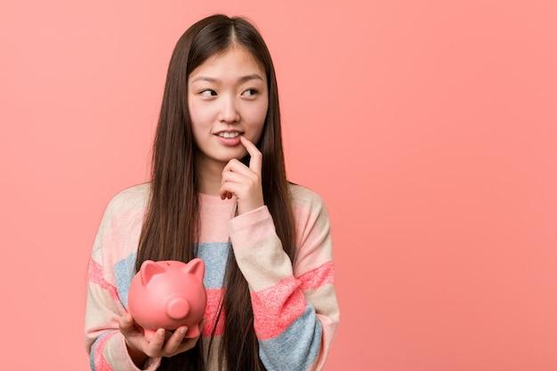 Jeune femme asiatique tenant une tirelire détendue en pensant à quelque chose en regardant un espace vide.