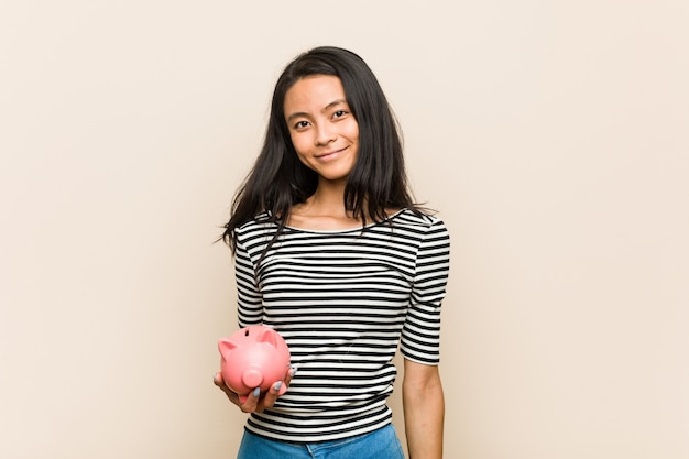 Jeune femme asiatique tenant une tirelire heureuse, souriante et joyeuse.
