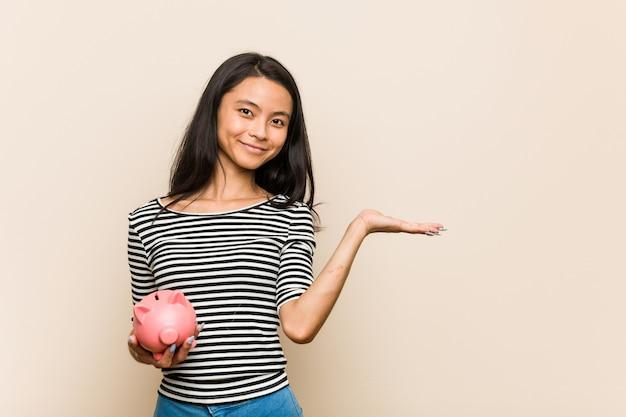 Jeune femme asiatique tenant une tirelire montrant un espace de copie sur une paume et tenant une autre main sur la taille.